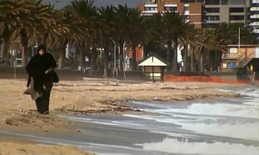 Woman in burqa walking along beach