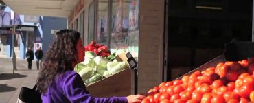Woman in purple top at fruit shop