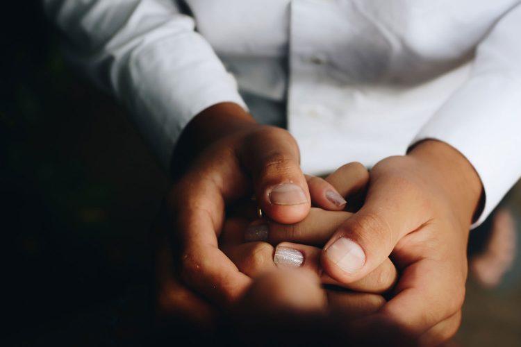 Doctor's hands claspling patient's