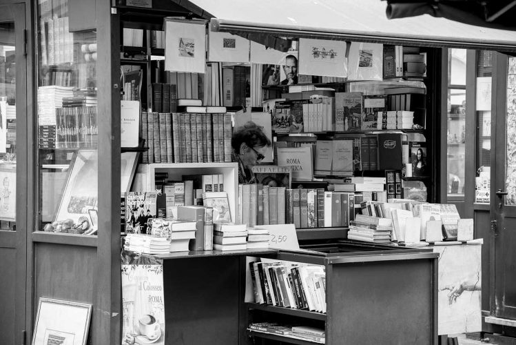 Black and white photo of bookshop with bookshop owner