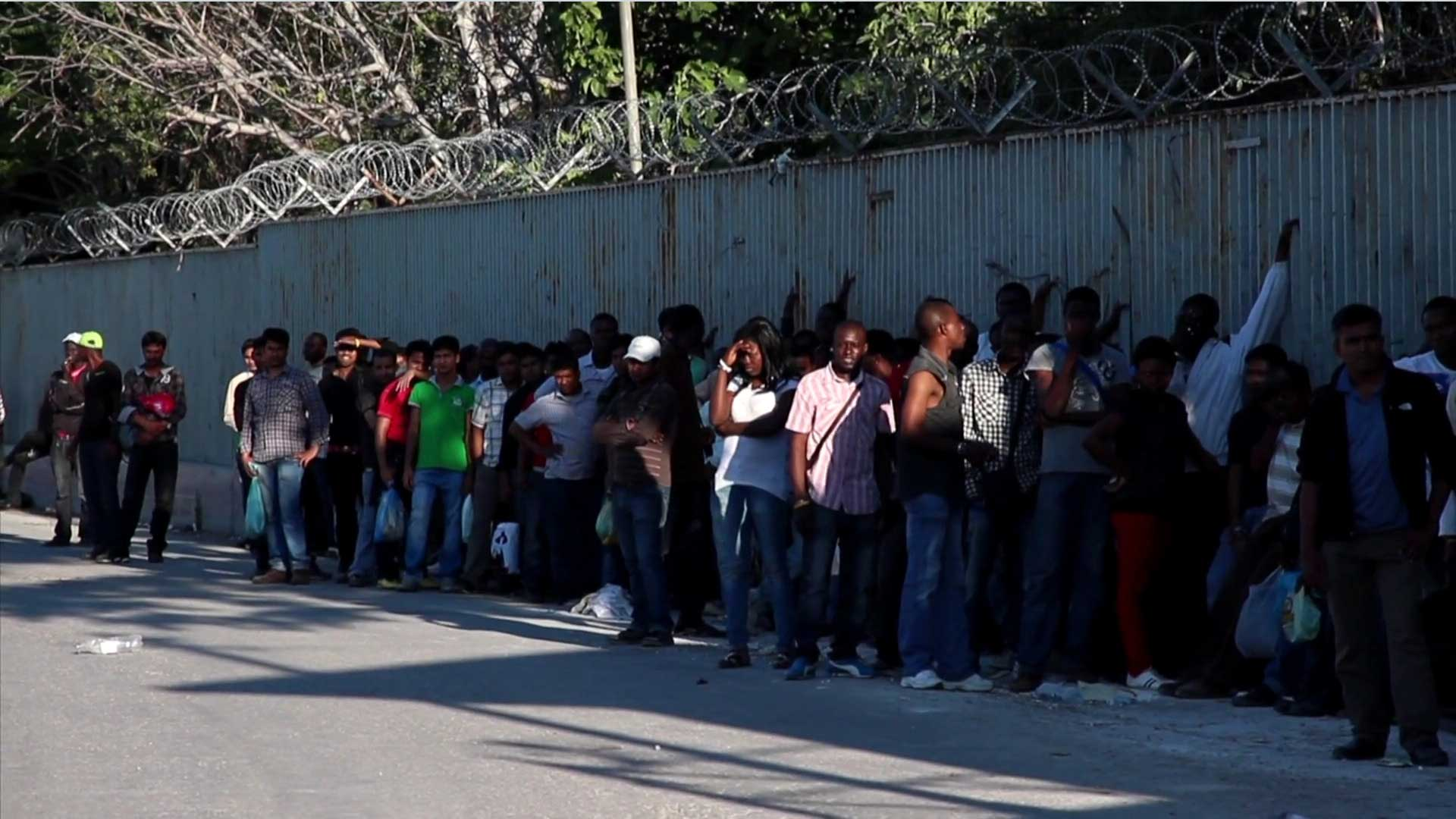 Long queue of people in front of a wall
