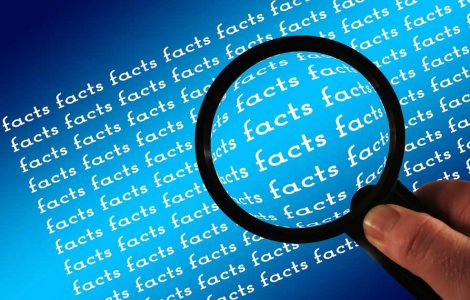 Magnifying glass with the word facts repeated multiple times
