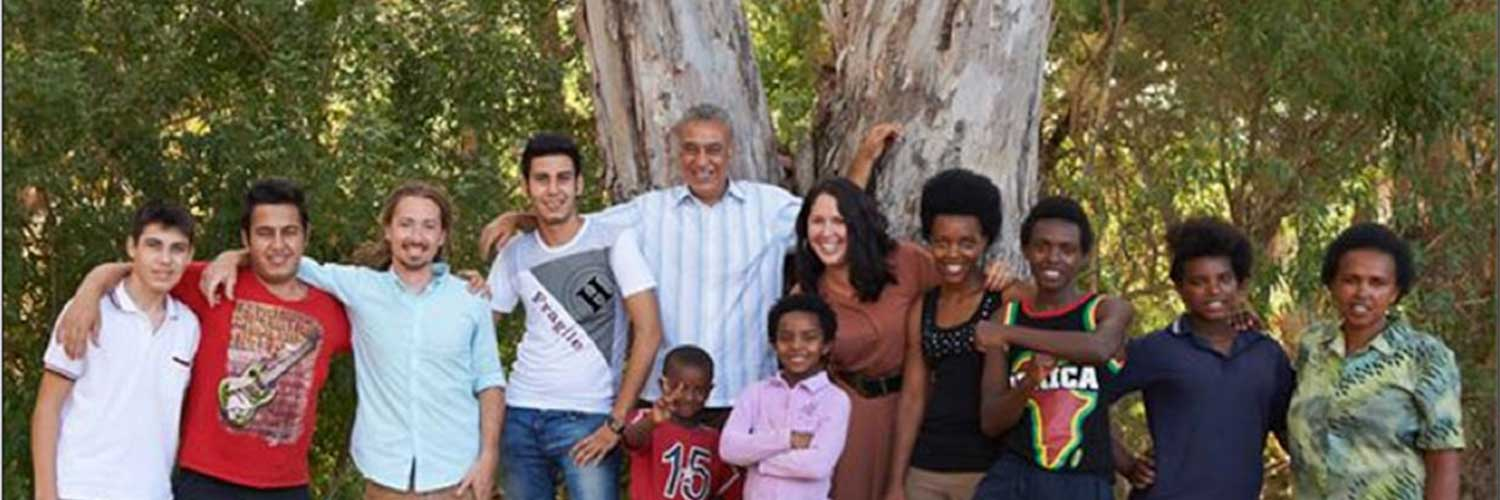 Group of people standing in front of tree smiling