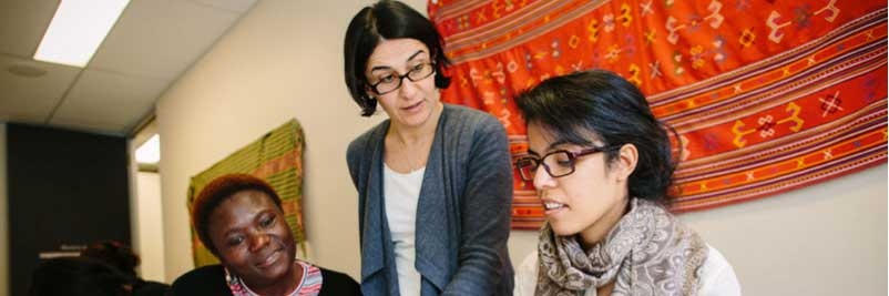 Three women with colourful rug in background