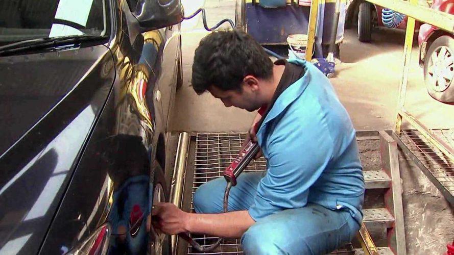 Man in blue uniform fixing car
