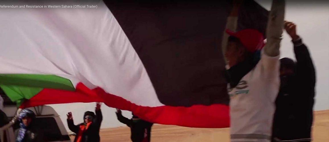 Men holding large independence flag