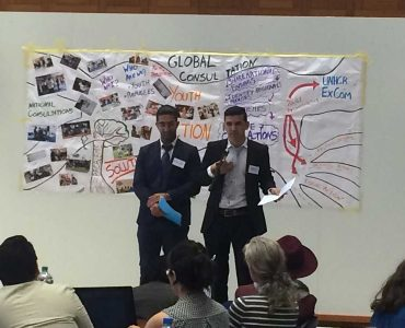 Arif and Arash in front of group of people with colourful diagrams on paper behind them