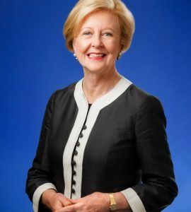Woman with short blonde hair in blue jacket with blue background