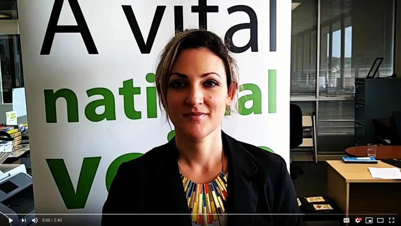 Video still of Rebecca Eckard with RCOA banner