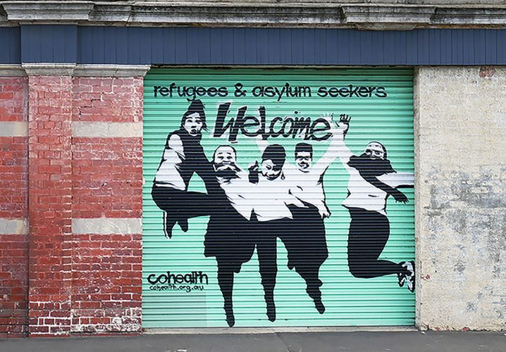 Green mural of figures jumping saying refugees and asylum seekers welcome