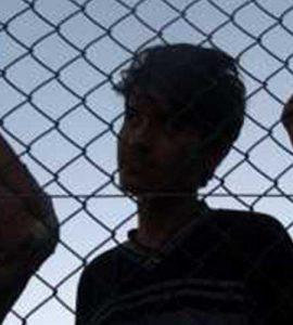 Dark silhouettes of men behind fence