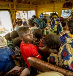 Boy in red T-shirt on crowded bus