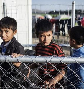 Children walking past fence