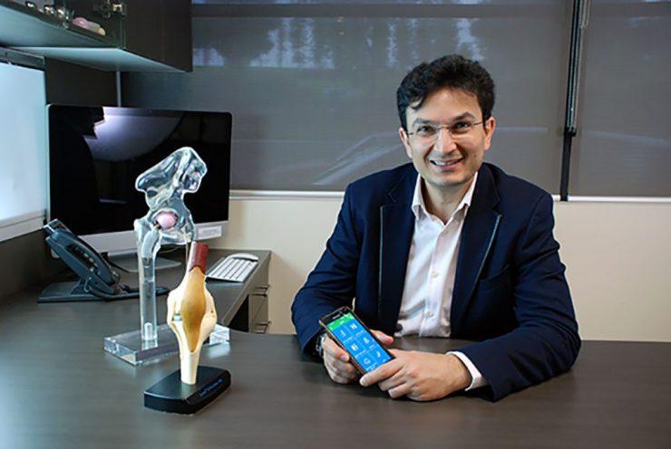 Dr Munjed Al Muderis holding phoone