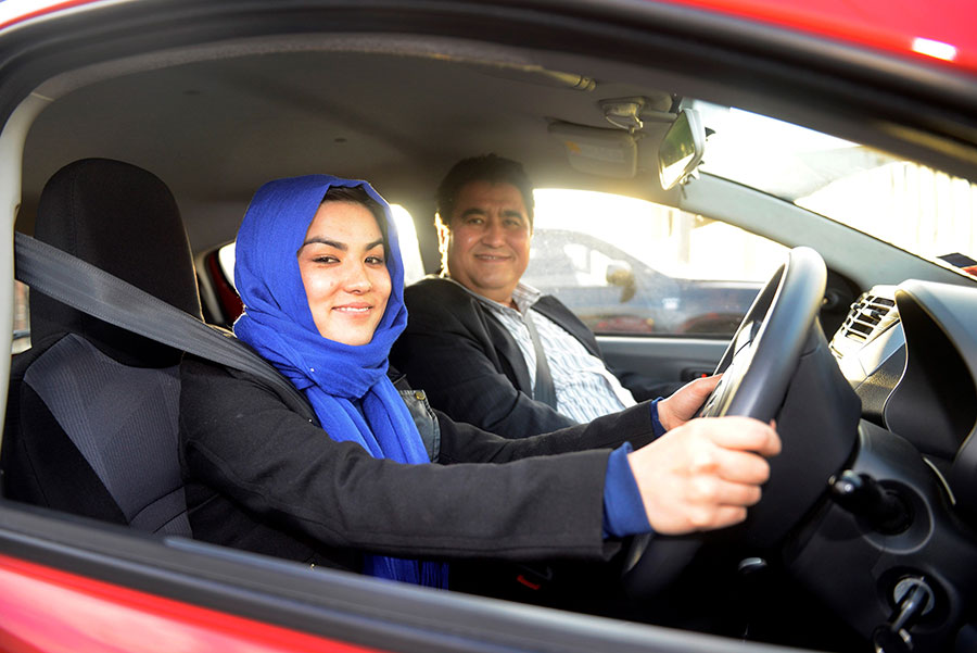 Smiling woman in blue headscarf next to man in red car
