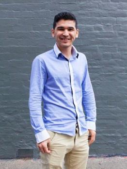 Arif Hazara standing against wall