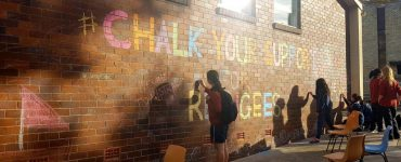 People chalking on a wall saying Chalk your support for refugees
