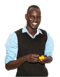 Dor in vest and blue shirt holding fruit