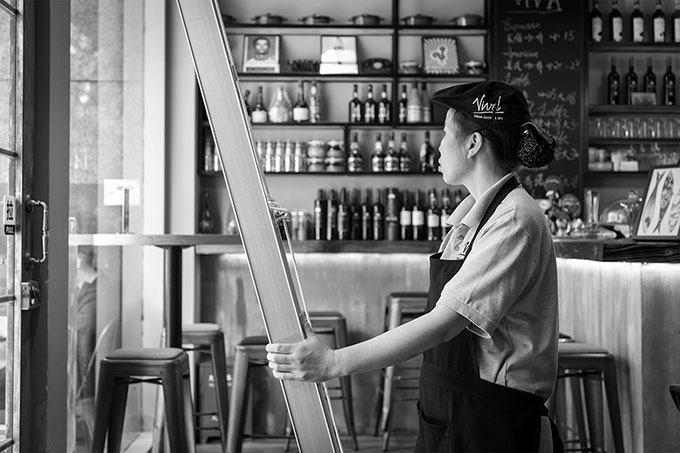Woman holding ladder in shop