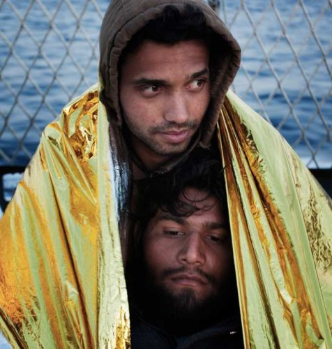 Two men huddling in yellow shelter