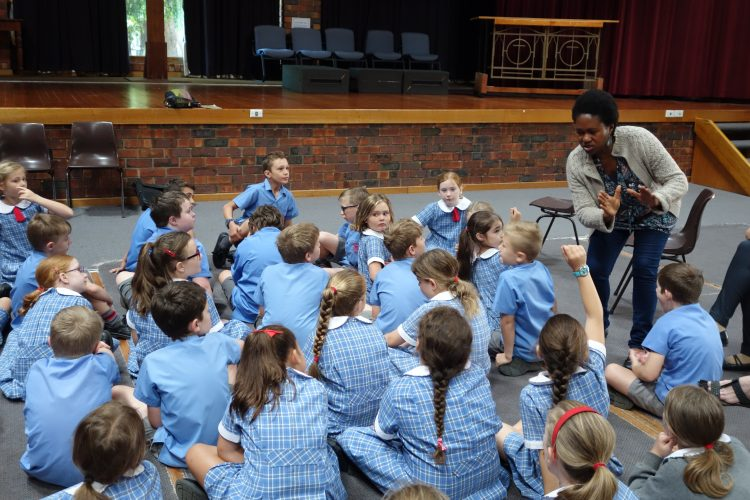 Presenter engaging girls in blue uniforms