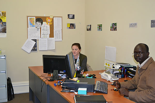 Two people in office, one man looking at camera and other looking at computer