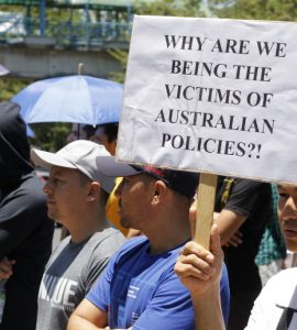 People protesting with placard saying why are we the victims of Australian policies?!
