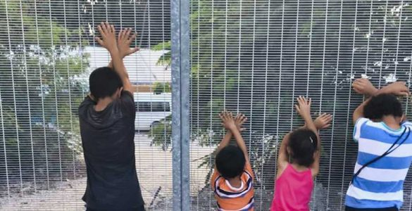 Children with backs towards camera and arms crossed in front of fence