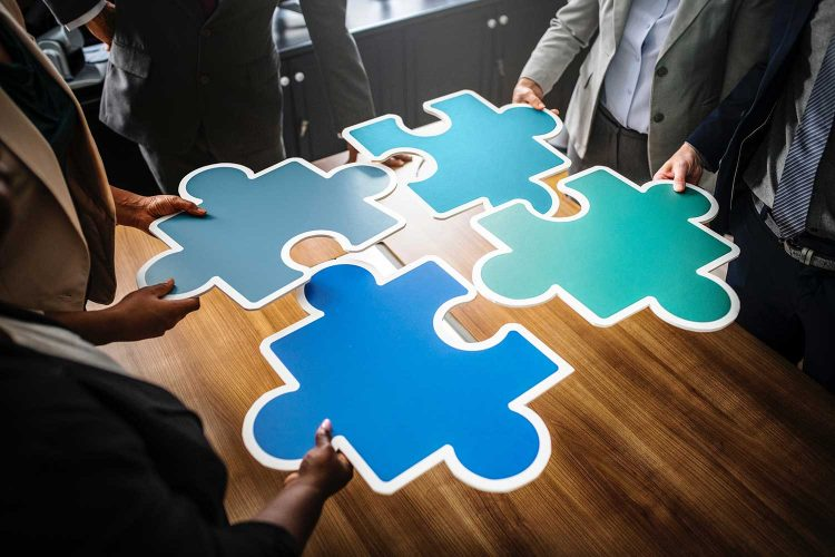 Hands holding together pieces of jigsaw over meeting table