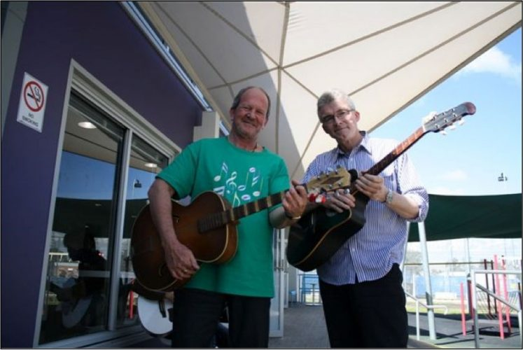 Two men holding guitars under shade sail
