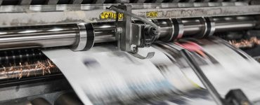 Newspapers coming out of printing press