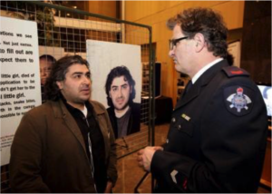 Man in glasses speaking to refugee with background photo