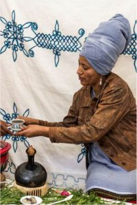 Woman with blue ruban receiving cup of tea