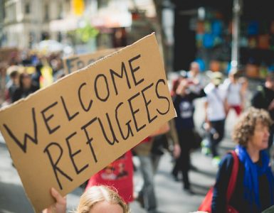 Large cardboard Welcome refugees sign in protest
