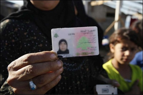 Woman holding identity card with child in background