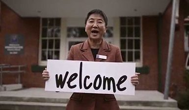 Woman holding welcome sign
