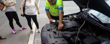 Man looking at engine of car under hood with two people behind him