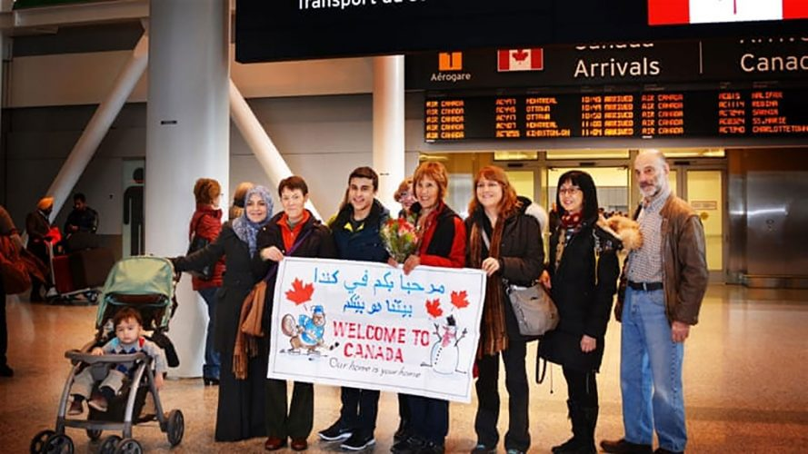 Group of Canadians holding welcome to Canada sign in airport