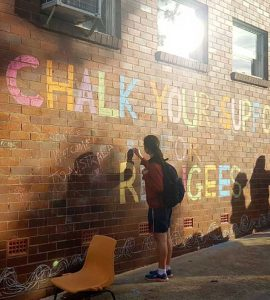 Children writing on wall saying Chalk your support for refugees