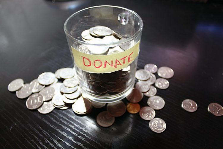 Cup of coins with donate sticker