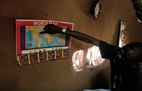 Man pointing at world map on wall