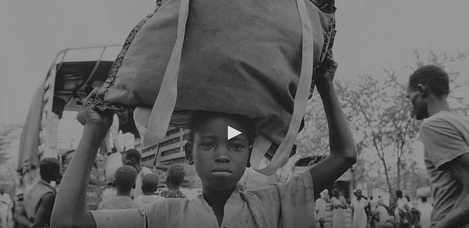 Black and white image of African boy with sack over his head
