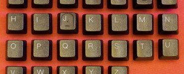 Keyboard letters spelling out alphabet across red background