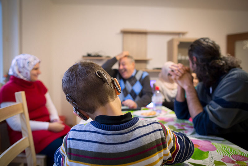Young boy with hearing aid sitting with family