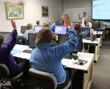 Group of adults raising their hands in a classroom with computers