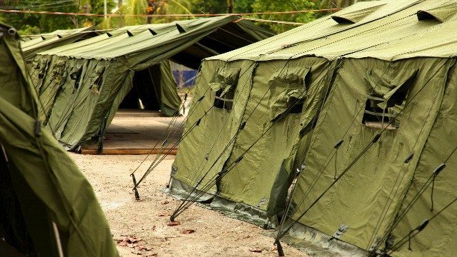 Series of big khaki green tents on gravel ground, with palms and trees in the backgrouund.