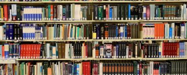 Library bookshelves with a large number of academic books on them.