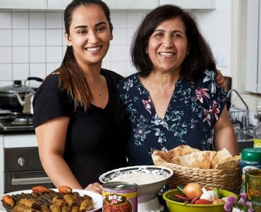 Rnita and her mother in front of a table of food