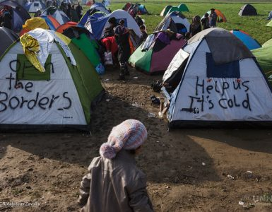 Woman standing in front of two tents, one saying open the borders, the other help us it's cold