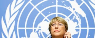 Michelle Bachelet in front of blue UN logo background